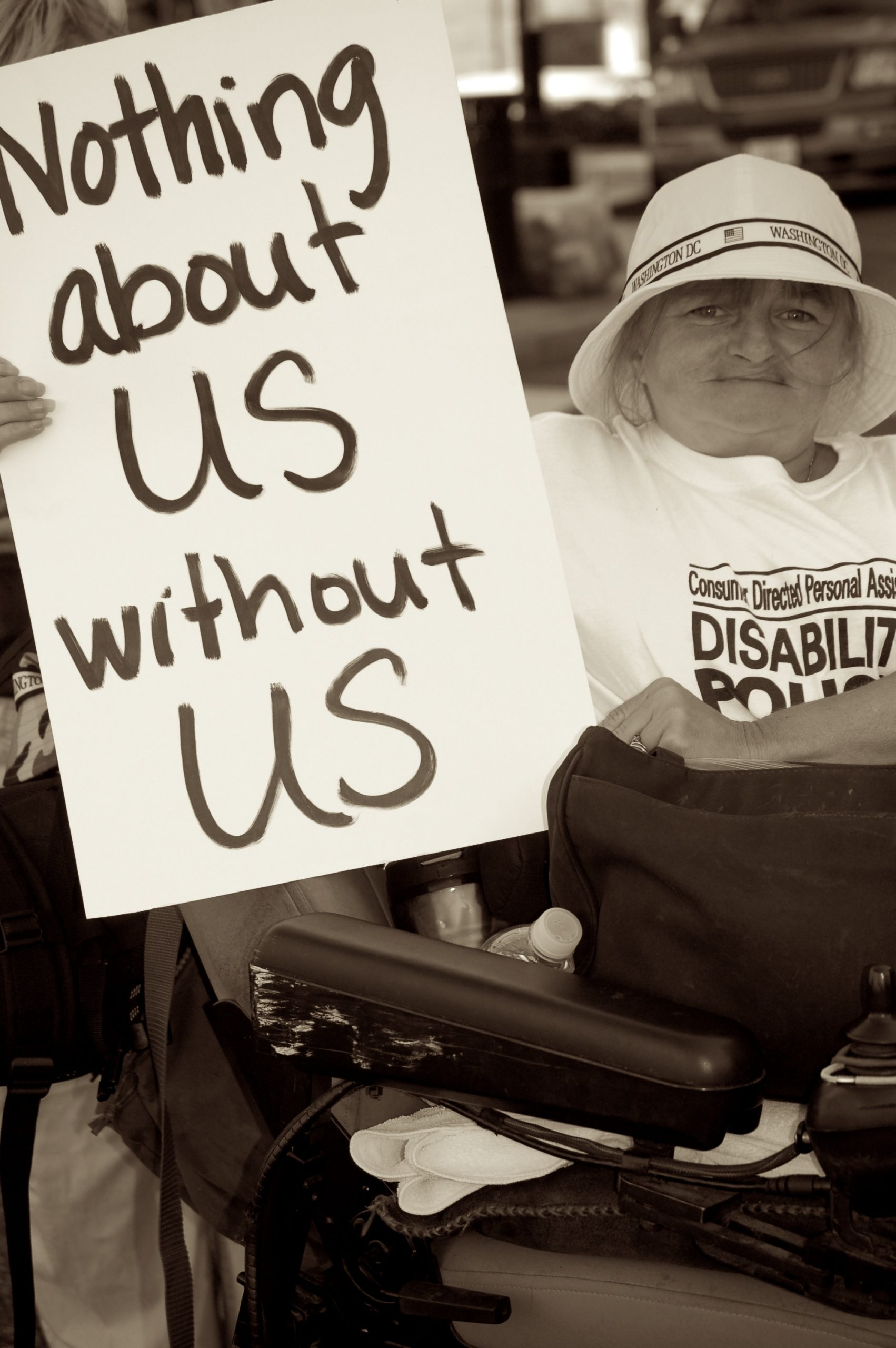 """Photo of woman in wheelchair holding sign saying """"nothing about us without us"""""""